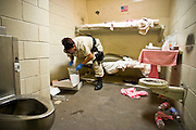 """24 MARCH 2004 - PHOENIX, AZ, USA: Maricopa County Sheriff's Dept Detention Officer C. Lopez inspect a juvenile prisoner's jail cell in the Maricopa County Jail in Phoenix, AZ, March 24, 2004. The juveniles volunteer to serve Maricpoa County Sheriff Joe Arpaio's chain gang. The sheriff, who claims to be """"the toughest sheriff in America,"""" has chain gangs in both the men's and women's jails and now has a chain gang for juveniles sentenced and serving time as adults in the county jail system. The sheriff claims it is the only juvenile chain gang in the country.   PHOTO BY JACK KURTZ"""