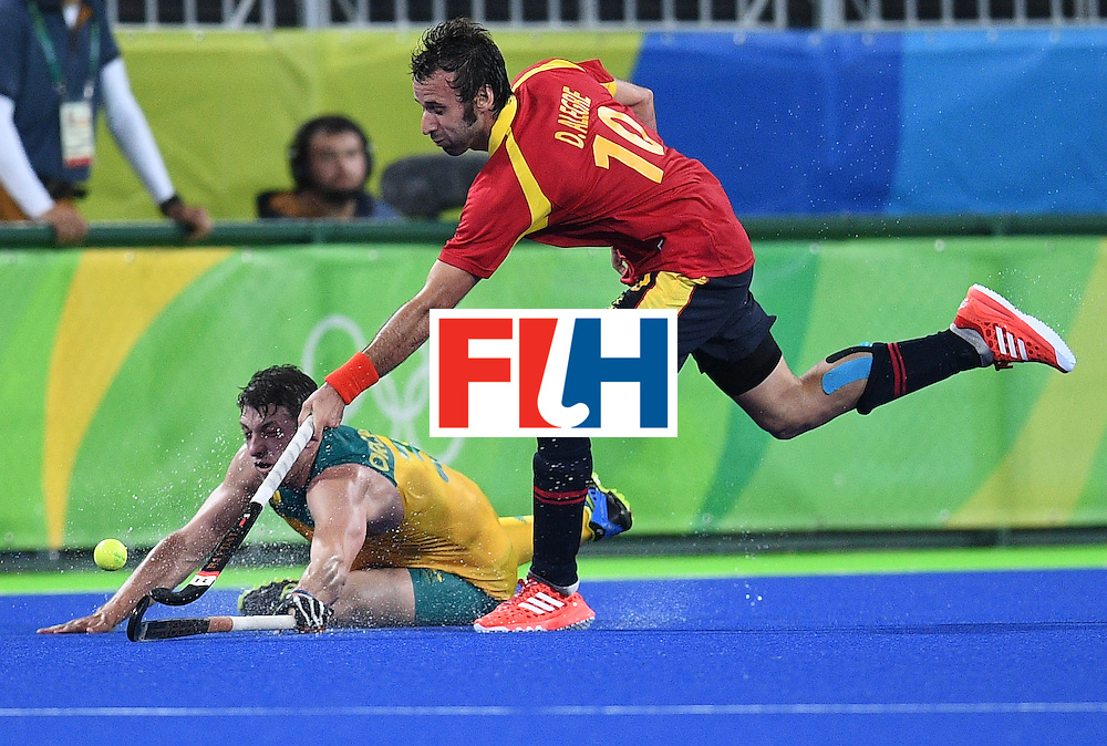Australia's Simon Orchard falls as Spain's David Alegre stretches for the ball during the men's field hockey Australia vs Spain match of the Rio 2016 Olympics Games at the Olympic Hockey Centre in Rio de Janeiro on August, 7 2016. / AFP / MANAN VATSYAYANA        (Photo credit should read MANAN VATSYAYANA/AFP/Getty Images)