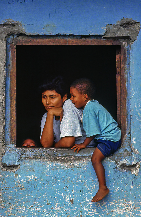 ca. 1980-1995, Colombia --- A mother and child sit at a window, Bahila Solano, Choco, Colombia. | Location: Bahila Solano, Choco, Colombia.  --- Image by © Jeremy Horner/Corbis