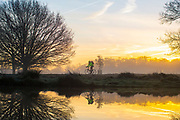 UNITED KINGDOM, London: 18 December 2017 A cyclist rides past a small lake in front of a stunning sunrise in Richmond Park, London this morning. Rick Findler / Story Picture Agency