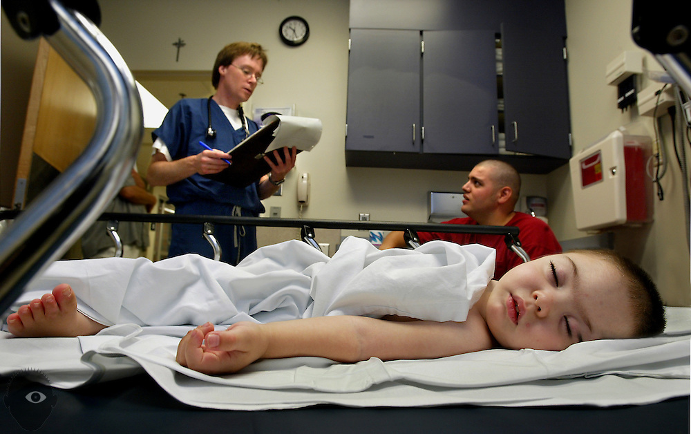 Isaac Velazquez rests while his father Nathan Velazquez (top right) talks about his son with Dr. Chris Strear within the emergency room at Emmanuel Lutheran Hospital.  Isaac was born with spina bifida which comes with seizures and brings him regularly to the hospital...