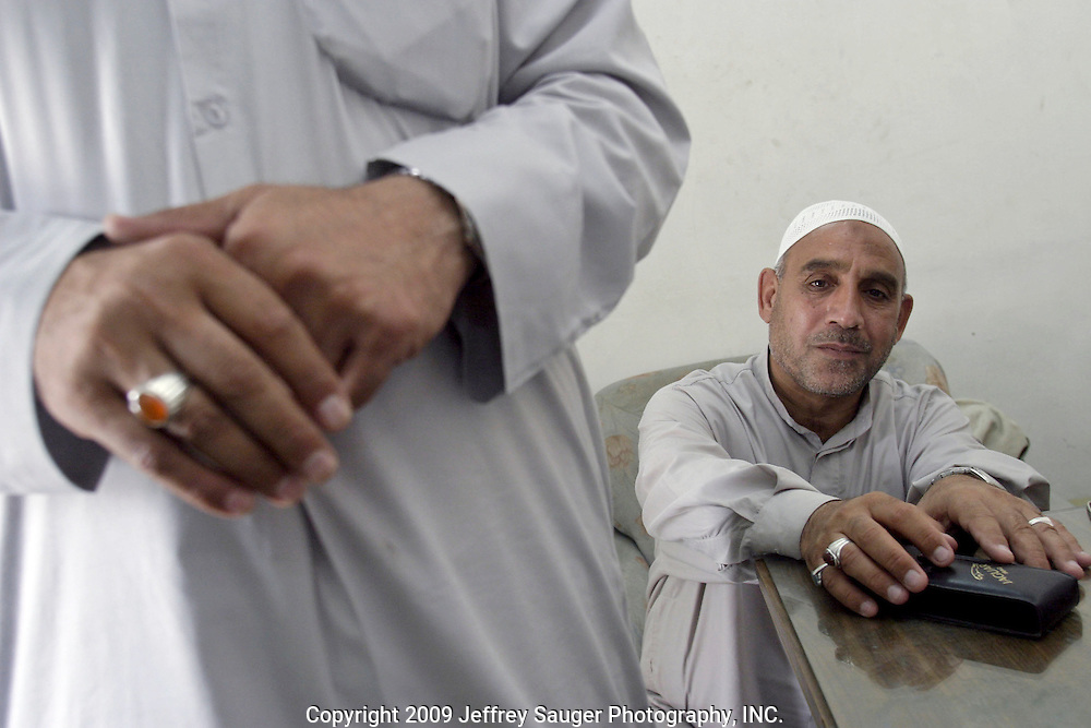 "Shiite religious men, Abu Soumhi, left, and Abu Fatimha, who would only give nicknames for rear of reprisals against them, talk about their lives at the Imam Aba Al Fa Thill Abbas Holy Shrine in Karbala, Iraq, Monday, July 21, 2003. Shiite, Soumhi was in prison for 13 years and Fathimha for 8 just for practicing their faith. They have helped to found a group for former prisoners...Fatimha said in 1991 Saddam killed women and children in and near the shrine and bulldozed their bodies into mass graves. Doctors Without Borders has promised to help identify the 1000's of bones, but, they've had no luck in finishing the daunting task...""The people do not have the trust they had for America,"" he said.""The American government says it catches Aziz, Chemical Ali and all these others but, never shows these criminals to us to prove it.'Why all the secrecy? It's like a play or movie from Hollywood.""..He said their people do not want to be the rulers; they just want the freedom to speak their minds and not be attacked.. .They are part of a group of several men whose job it is to administer, organize, secure, lead tours, make announcements, keep lost and found items safe, etc. at the Imam Hussein and Imam Aba Al Fa Thill Abbas Holy Shrines in Karbala who have not been paid for 3 months since the fall of Saddam Hussein."