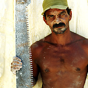 A man (who did not wish to be identified) works at a limestone cooperative quarry, just outside the city of Matanzas, Cuba. The stone is cut with long-toothed handsaws, and carried through the quarry to a waiting truck. Cubans can donate their time to cut bricks from the stone, and are allowed to take a portion of the product home in reparation.