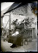 content elderly woman sitting in backyard France circa 1920s