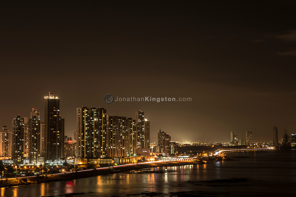 Night view of Panama city's skyline rising over the Pacific ocean.