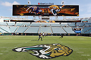 Players warm up before the Jacksonville Jaguars game as the logos of the competing teams appear on the scoreboard and also painted on the field  (Jaguars) before the Jacksonville Jaguars 2016 NFL week 3 regular season football game against the Baltimore Ravens on Sunday, Sept. 25, 2016 in Jacksonville, Fla. The Ravens won the game 19-17. (©Paul Anthony Spinelli)