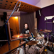 A man plays drums in a sound booth during a sound check in a recording studio.