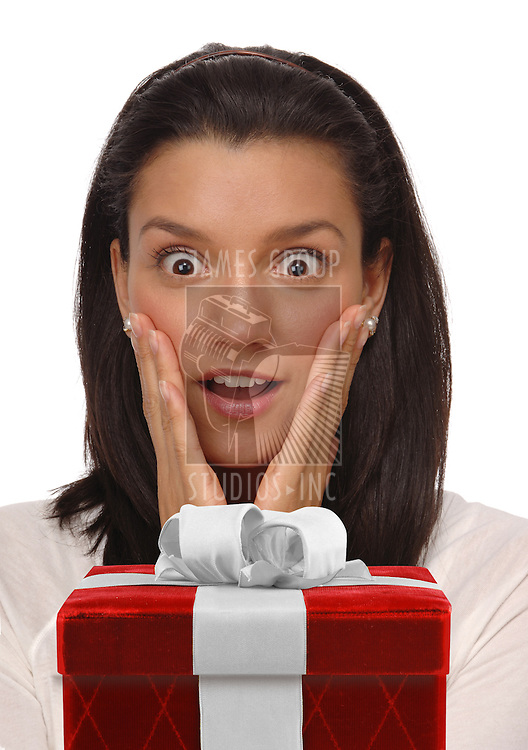 Beautiful, young woman on a white background with an expression of happy surprise staring at a gift box