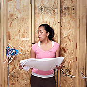 Woman holding building plans looking at an electrical box