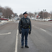 A single St. Paul police officers stands at the intersection of University Avenue and Lexington Parkway during a  #ReclaimMLK march organized by Black Lives Matter Minneapolis in conjunction with Ferguson Action's national day of action on the Rev. Martin Luther King, Jr. national holiday in St. Paul, Minnesota on January 19, 2015.  <br /> <br /> The event also was attended by the family of Marcus Golden, who was killed by St. Paul police officers last week. <br /> <br /> Photo by Angela Jimenez for MPR<br /> photographer contact 917-586-0916