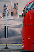 The rear of a red London Routemaster bus beneath a property developer's billboard showing a large aerial image of London skyscrapers in low cloud.