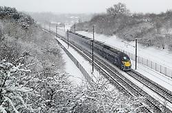 A Eurostar train passes through Ashford, Kent, following heavy overnight snowfall which has caused disruption across Britain.