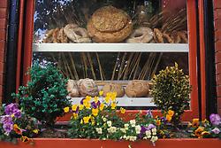 Bakery pastry shop display window breads rolls flowers cookies.