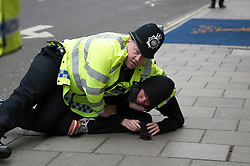 London News Pictures. 26/03/2011. A policeman pins down a protester in front of The Ritz Hotel in central London on 26/03/2011 during a massive Anti-cuts march in London. Photo credit should read Michael Graae/London News Pictures
