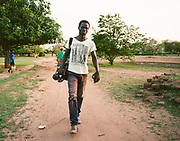 "NUBA MOUNTAINS, SUDAN – JUNE 9, 2018: Filmmaker Yassin Hassan walks through Kouda, the cultural center of Hieban county.<br /> <br /> In 2011, the government of Sudan expelled all humanitarian groups from the country's Nuba Mountains. Since then, the Antonov aircraft has terrorized the Nuba people, dropping more than 4,080 bombs on hospitals, schools, marketplaces and churches. Today, vestiges of the Antonov riddle the landscapes of daily life, where more than 1 million Nuba live in famine conditions – quietly enduring the humanitarian blockade intended to drive them out of the region. The skies are mostly clear. Yet the collective memory of the bombings remains an open wound, and the Antonov itself a persistent threat. So frequent were the attacks that the Nuba nicknamed the high flying aircraft and its dismal hum: ""Gafal-nia ja,"" they would declare, running to the hillsides. ""The loss of appetite has come."""
