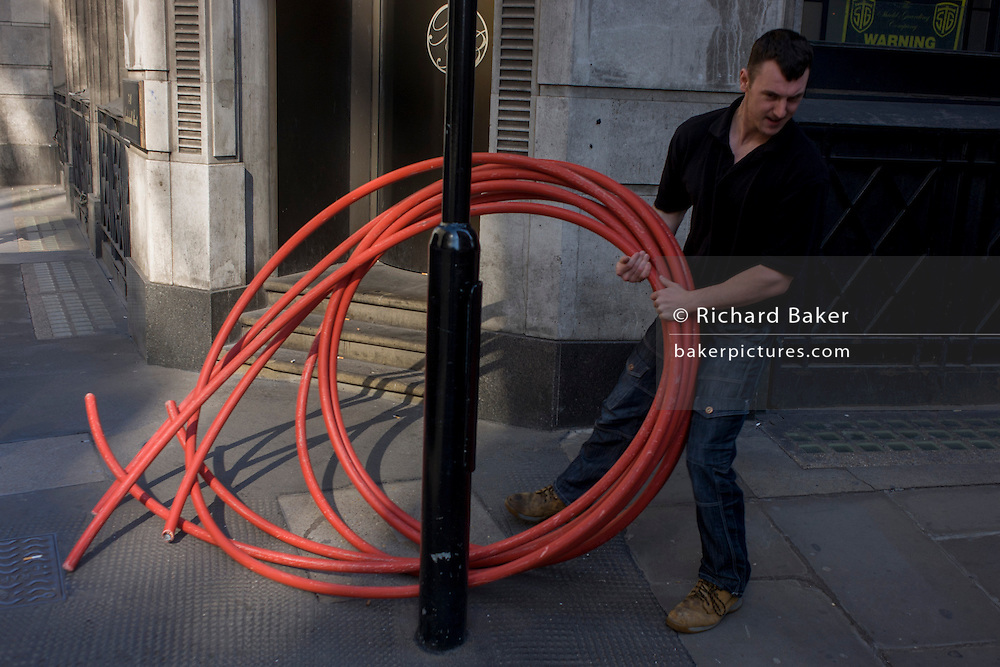 A  workman drags a coil of heavy piping through a street in the City of London.