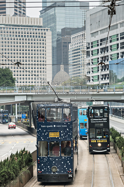 Historic double decker trams travel down Queensway Road in the central district of Hong Kong.