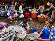 "12 JANUARY 2016 - BANGKOK, THAILAND: Workers clean and descale fish while they wait for customers in Khlong Toey Market in Bangkok. Khlong Toey (also called Khlong Toei) Market is one of the largest ""wet markets"" in Thailand. The market is located in the midst of one of Bangkok's largest slum areas and close to the city's original deep water port. Thousands of people live in the neighboring slum area. Thousands more shop in the sprawling market for fresh fruits and vegetables as well meat, fish and poultry.         PHOTO BY JACK KURTZ"