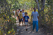 Tourists follow a guide as they hike through Komodo National Park, Indonesia