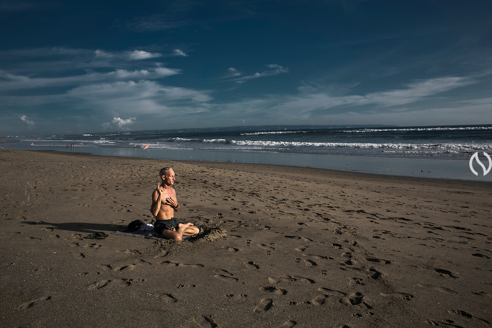 BALI, INDONESIA; APRIL 18, 2015: An expat meditates at Batu Belig beach, Bali, Indonesia on Saturday, April 18, 2015.