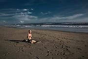 BALI, INDONESIA; APRIL 18, 2015: An expat meditates at Batu Belig beach, Bali, Indonesia on Saturday, April 18, 2015.