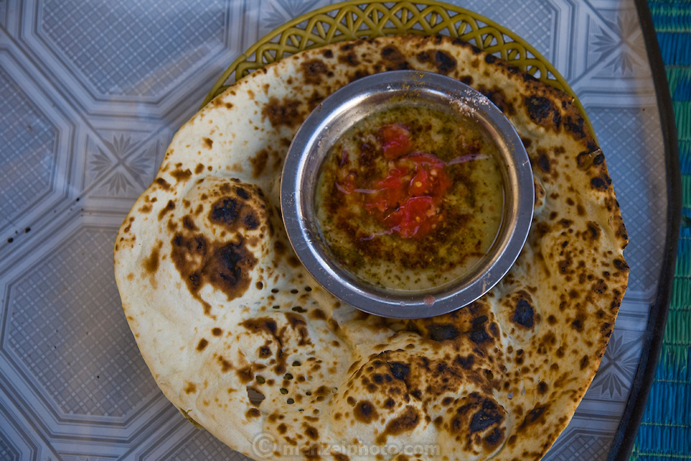 A breakfast plate of flatbread and ful (fava beans, oil, and tomatoes)  in Shibam, Hadhramawt, Yemen.
