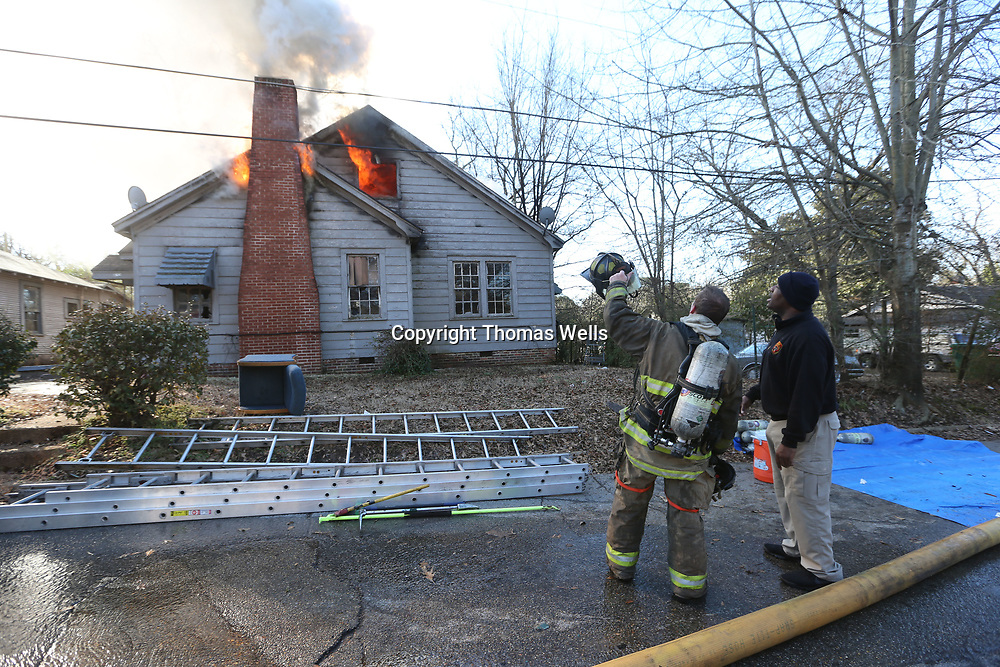 Tupelo firemen step back as the department moves a ladder truck into place to help battle a house fire on Wlker Street in Tupelo Monday morning.