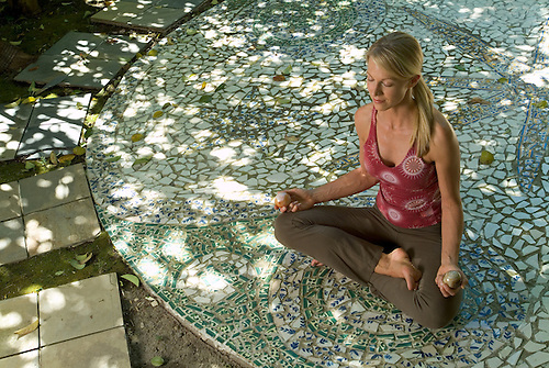 Wellness Image Of Young Woman Meditating On Mosaic Patio.