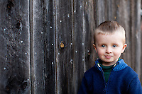 Cute portrait of a young boy (Zeb Whitlock) outside a barn in Vermont