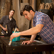 Alex Geriner, woodworker and owner/founder of Doorman Designs and employee Cody Mower (in back) in the woodshop in the Lower Garden District in New Orleans. Geriner works primarily with specifically Southern reclaimed material, such as cypress and wrought iron. In this image they are putting finishing touches of a bed headboard. For more information: http://www.doormandesigns.com