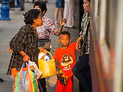 20 MARCH 2015 - CHACHOENGSAO, CHACHOENGSAO, THAILAND:  Passengers get on a 3rd class train in Chachoengsao. The State Railways of Thailand (SRT), established in 1890, operates 4,043 kilometers of meter gauge track that reaches most parts of Thailand. Much of the track and many of the trains are poorly maintained and trains frequently run late. Accidents and mishaps are also commonplace. Successive governments, including the current military government, have promised to upgrade rail services. The military government has signed contracts with China to upgrade rail lines and bring high speed rail to Thailand. Japan has also expressed an interest in working on the Thai train system. Third class train travel is very inexpensive. Many lines are free for Thai citizens and even lines that aren't free are only a few Baht. Many third class tickets are under the equivalent of a dollar. Third class cars are not air-conditioned.    PHOTO BY JACK KURTZ