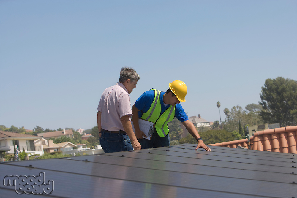 Maintenance workers stand with solar array on rooftop in Los Angeles California