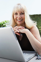 Woman Using Laptop in Garden