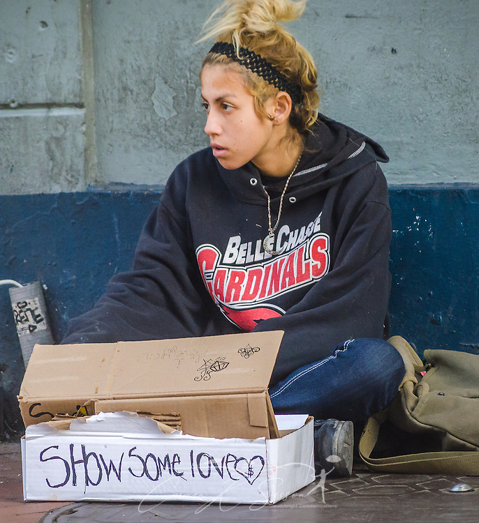 Kat Walsh panhandles on Bourbon Street, Nov. 15, 2015, in New Orleans, Louisiana. Walsh, 20, said she is homeless and sleeps on nearby St. Louis Street. She comes to the French Quarter in the daytime hoping tourists will give her money, but by late afternoon, her box was still empty. (Photo by Carmen K. Sisson/Cloudybright)