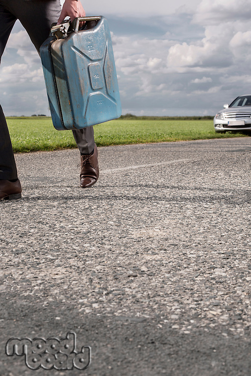Low section of businessman carrying gasoline can with broken car in background at countryside