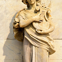 Terpsichore Playing Lyre in Old Town, Cartagena, Colombia<br /> There are four gorgeous marble carvings on the Heredia Theater façade.  They are all the daughters of Zeus, the Olympian ruler of the gods. This woman playing a lyre is Terpsichore.  She was the muse of dancing in Greek mythology.  Additional depictions of muses can be seen inside the theater, as well as an amazing Italian staircase.