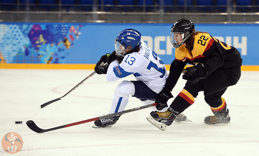 Feb 16, 2014; Sochi, RUSSIA; Finland forward Rikka Valila (13) battles for the puck with Germany forward Kerstin Spielberger (22) in the women's ice hockey classifications round during the Sochi 2014 Olympic Winter Games at Shayba Arena.
