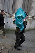A workman carries a load wrapped in plastic outside the Bank of England in the City of London, the capital's financial district, on 28th January 2020, in the City of London.