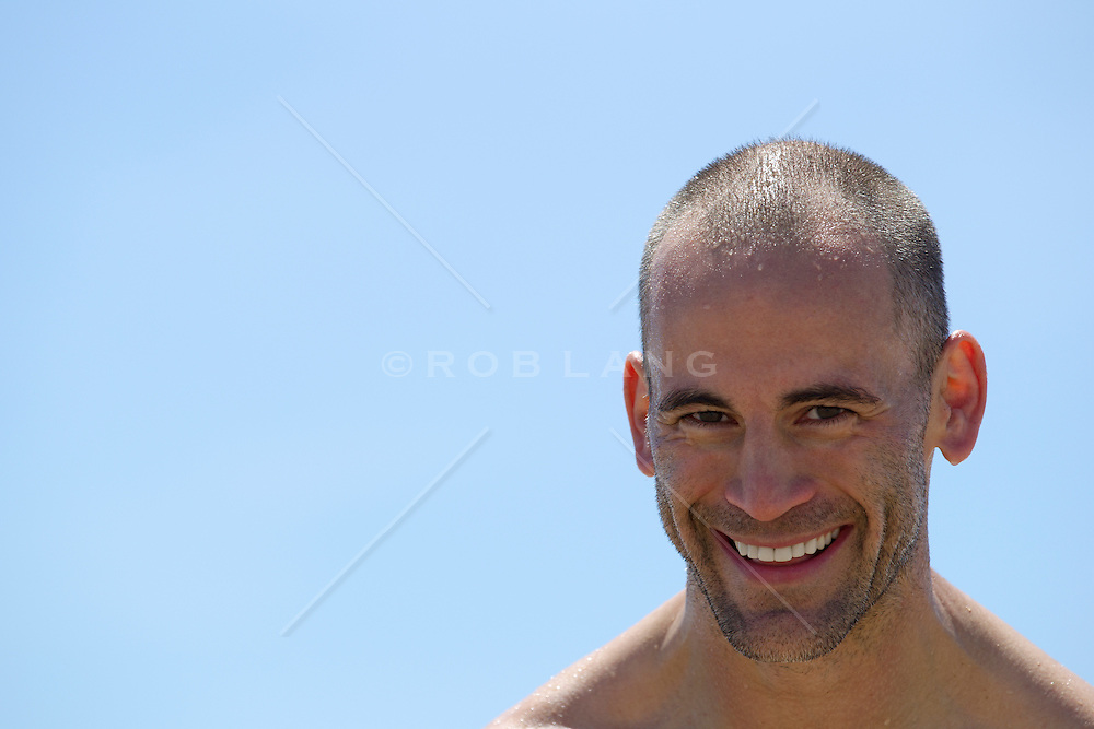portrait of a handsome man with a shaved head at the beach