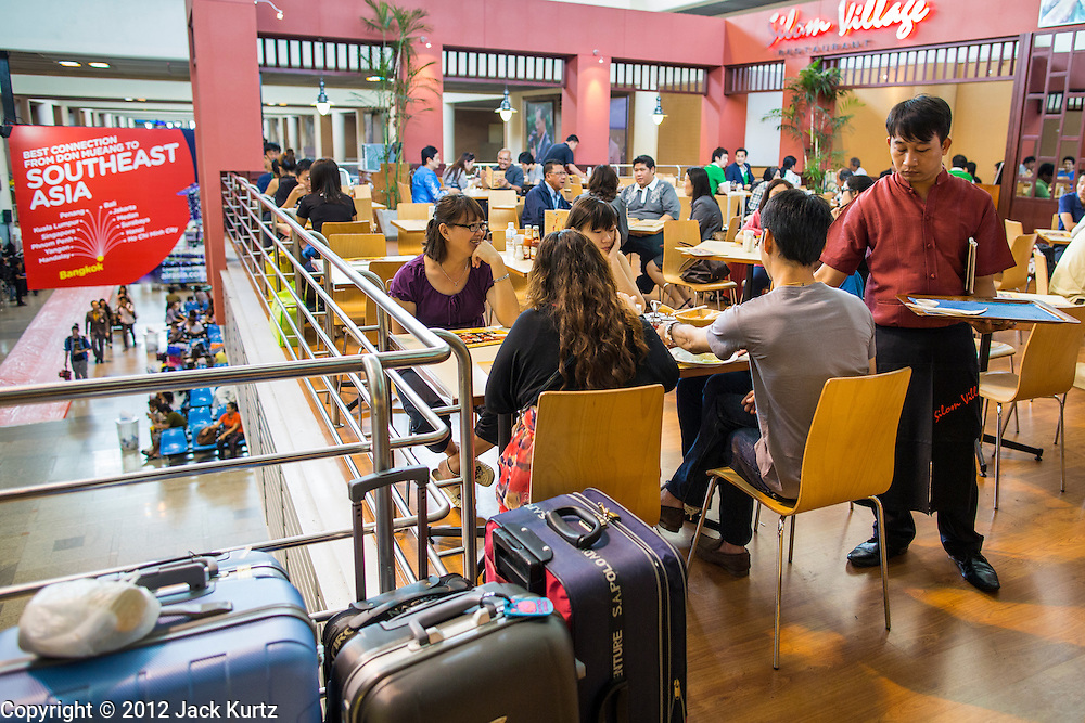 01 OCTOBER 2012 - BANGKOK, THAILAND:  People eat in one of the restaurants in Don Mueang International Airport in Bangkok during the reopening Monday. Don Mueang International Airport is the smaller of two international airports serving Bangkok, Thailand. Suvarnabhumi Airport, opened in 2006 is the main one. Don Mueang was officially opened as a Royal Thai Air Force base on 27 March 1914 and commercial flights began in 1924. Don Mueang Airport closed in 2006 following the opening of Bangkok's new Suvarnabhumi Airport, and reopened as a domestic terminal for low cost airlines after renovation on 24 March 2007. Closed during the flooding in 2011, Don Mueang was again renovated and reopened in 2012 as the airport for low cost airlines serving both domestic and international passengers. On Monday, Air Asia, Asia's leading low cost airline, transferred all of their flight operations to Don Mueang and the airport was officially reopened. Suvarnabhumi International Airport is already over capacity and Don Mueang's importance as a hub is expected to grow.   PHOTO BY JACK KURTZ