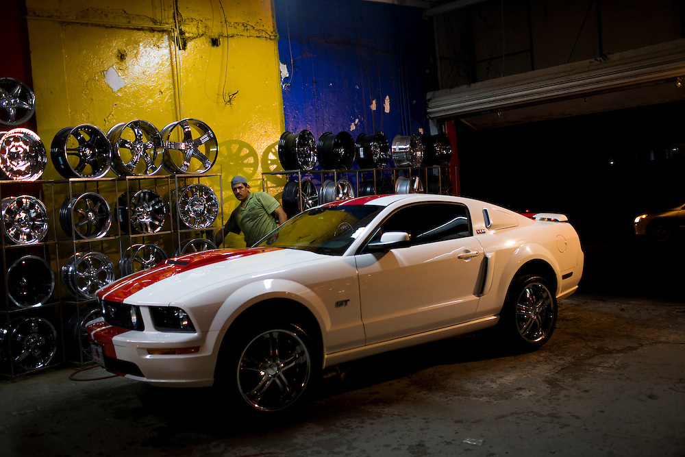 A worker puts new rims on a tricked out Mustang at a workshop in Culiacan, Mexico.  The streets of Culiacan are filled with fancy, modified cars like this mustang.  Mexico's narco culture is marked by ostentatious displays of wealth, like these fancy cars.