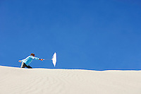Boy (10-12) holding beach umbrella in wind on sand dune