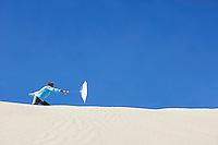 Boy (10-12) holding beach umbrella in wind on sand dune