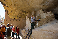 A US National Parks ranger talks to a group of visitors in the Balcony House ruins, Mesa Verde National Park, near Cortez, Colorado.