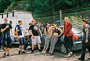 Girls with black and white checked trousers leaning on car in group of ravers, Halfway Quarry Brecon Wales, May 2017