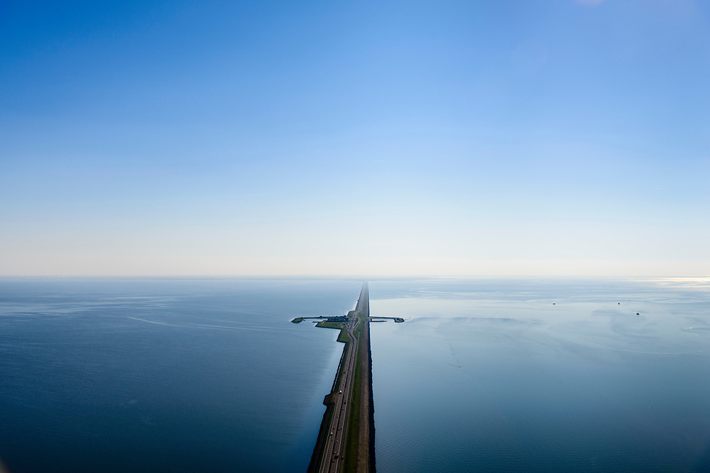 Nederland, Friesland, Gemeente Wonseradeel, 07-05-2018; Afsluitdijk ter hoogte van Breezanddijk, het voormalig werkeiland Breezand. Gezien naar de kust van Noord-Holland, aan de horizon. Waddenzee rechts, IJsselmeer links.<br /> Enclosure Dam at the height of Breezanddijk, former 'work island' Breezand, seen in the direction of the Noord-Holland coast at the horizon (32 kilometers away). IJsselmeer lake (right), the Wadden Sea (left)<br /> luchtfoto (toeslag op standard tarieven);<br /> aerial photo (additional fee required);<br /> copyright foto/photo Siebe Swart