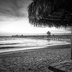 San Clemente CA Black and White photo with a straw tiki umbrella along the Southern California coastline. San Clemente is a popular coastal city in Orange County in the United States of America. Copyright ⓒ 2017 Paul Velgos with all rights reserved.