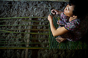 Nguyen Thi Phuong weaves a long bamboo mat on the dirt floor of her home. With the financial assistance of local NGO Anh Duong, Phuong and her family are able to purchase the materials and produce the mats, which have helped them raise their annual income signifigantly.