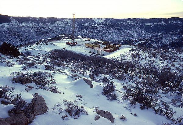 Stock photo of a snow covered oil and gas drilling rig on site in the mountains of Colorado.
