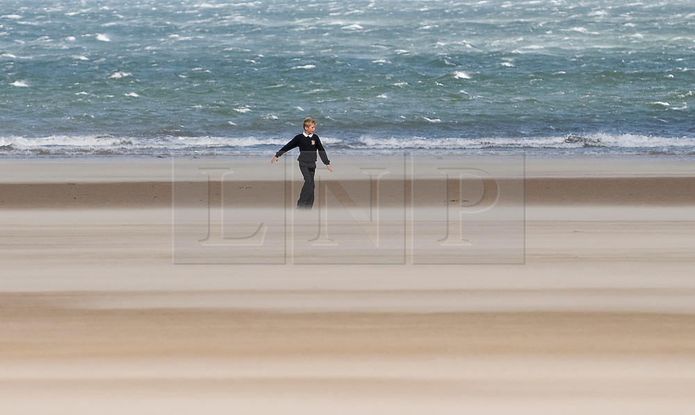 © Licensed to London News Pictures. 12/09/2011..Saltburn Beach, Saltburn, Cleveland, England...A young boy walks through blowing sand as strong winds blow across the beach at Saltburn in Cleveland...Photo credit : Ian Forsyth/LNP